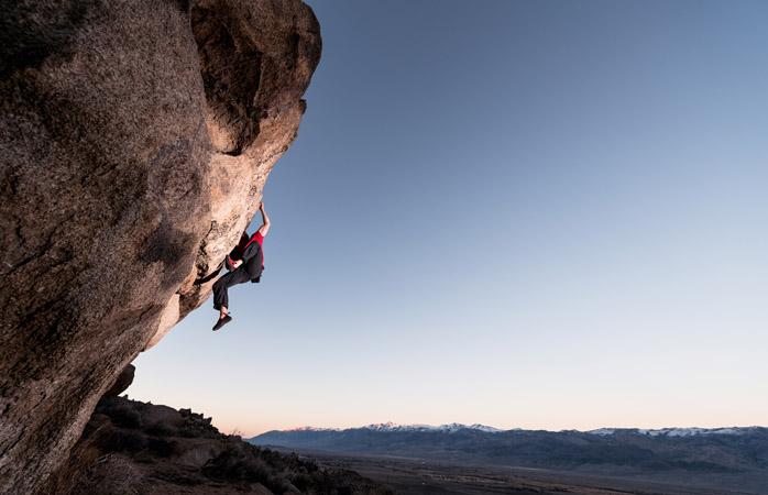 Ein Kletterer hängt an einem großen Felsbrocken hoch über Südkalifornien
