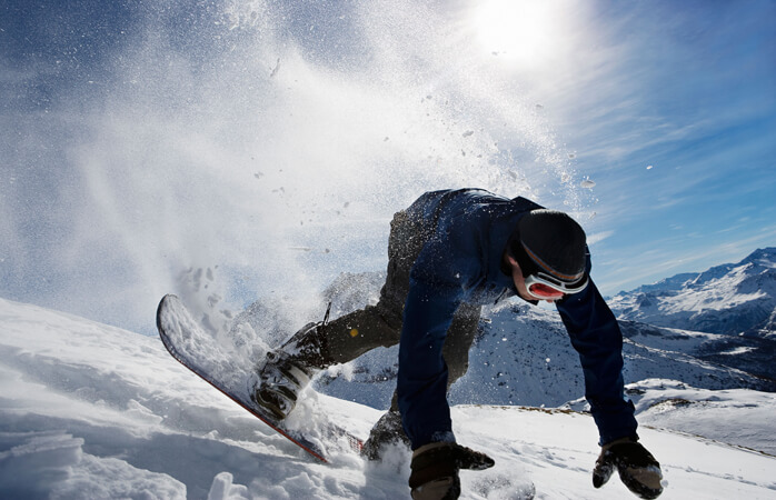 Ein Snowboarder verliert bei der Abfahrt auf einer Eispiste das Gleichgewicht