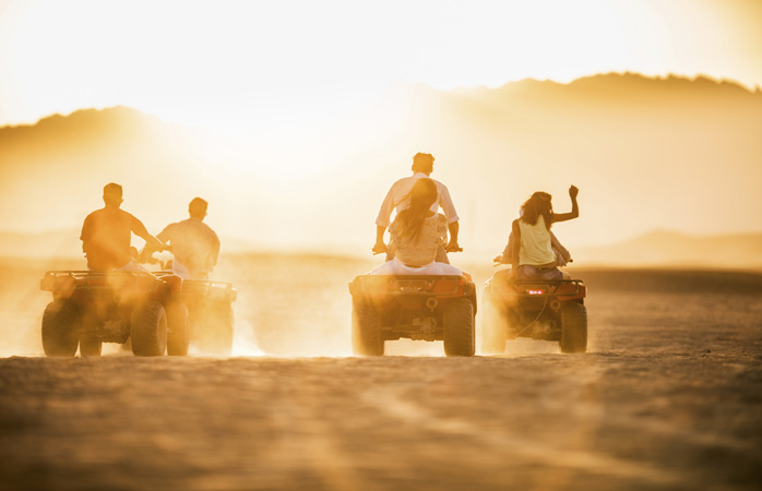 Freunde liefern sich in der Wüste ein heißes Quad-Rennen