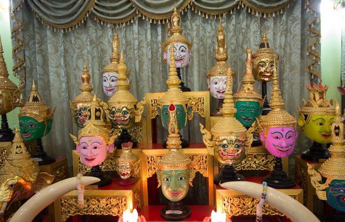 Bestaune die farbenprächtigen Masken im Tempel und auf dem Markt von Wat Tha Ka Rong